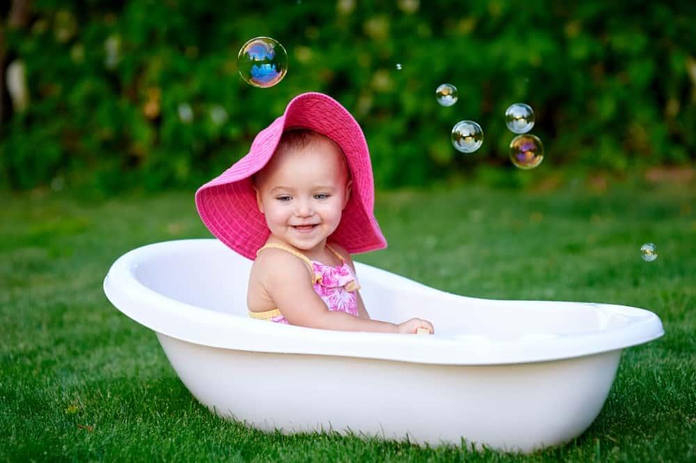 kind met roze hoed in bad