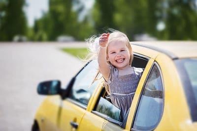 klein meisje op autovakantie zwaait uit het raam van een auto