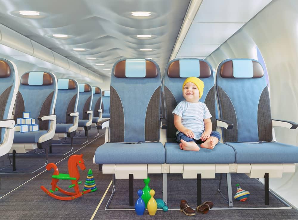 peuter in het vliegtuig omringd door speelgoed